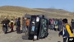Người biểu tình vây quanh một chiếc xe bị lật trong một cuộc biểu tình tại mỏ đồng Tinaya ở Peru, ngày 28/5/2012