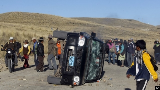 People surround an overturned car during a protest at the Tinaya copper mine owned by Swiss-based Xstrata plc in Espinar, Peru, May 28, 2012.