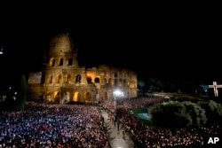Faithful attend the Via Crucis (Way of the Cross) torchlight procession celebrated by Pope Francis in front of the Colosseum on Good Friday in Rome, April 18, 2014.