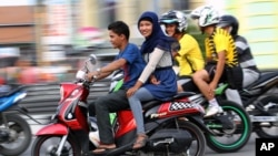 An Acehnese woman straddles on a motorbike on a road in Lhokseumawe, Aceh province, Indonesia. (AP Photo/Rahmat Yahya)