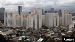 FILE - Rows of condominium buildings are seen behind a middle-class residential district in Mandaluyong, Metro Manila. The economy grew 6.4 percent in the first three months of the year, second only to China, July 4, 2012.