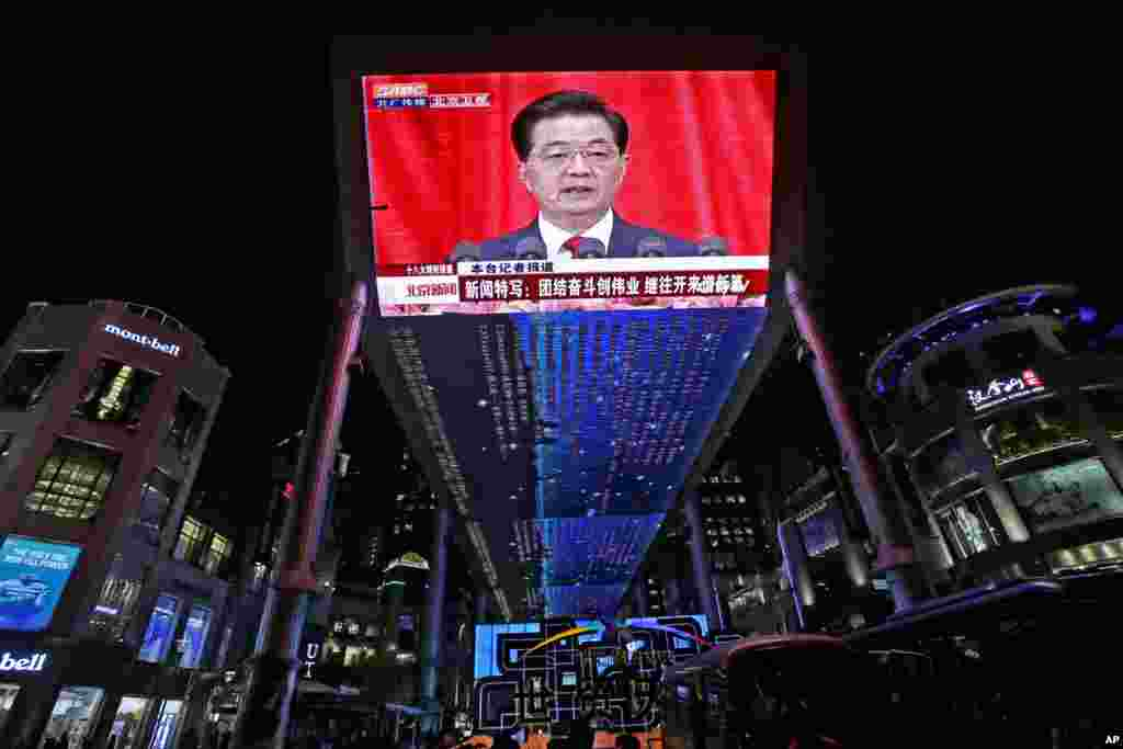 A huge screen shows a broadcast of Chinese President Hu Jintao speaking at the opening session of the 18th Communist Party Congress at the Great Hall of the People in Beijing, China, November 8, 2012.