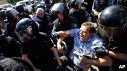 Cảnh sát ngăn cản một người phản đối cuộc diễu hành.