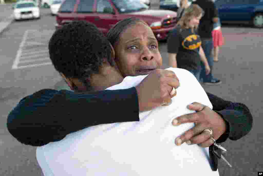 Shamecca Davis hugs her son, Isaiah Bow, who was an eye witness to the shooting, outside Gateway High School where witnesses were brought for questioning in Denver, Colorado, July 20, 2012.