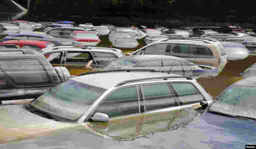 Cars emerge from the subsiding floods of the Danube river at a car dealership in Fischerdorf, Germany, June 10, 2013.