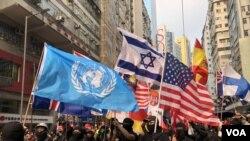 一批參與香港9-29全球抗極權遊行的示威者,高舉聯合國及世界各國的旗幟,呼籲國際社會共同對抗中國極權。(攝影: 美國之音湯惠芸)