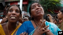 Indian women cry at the site of a building collapse where their relatives are stuck inside the debris, in Secunderabad outside Hyderabad, India, July 8, 2013.