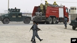 Afghan policemen keep watch during an attack by insurgents at a police training base in Kandahar, April 7, 2011