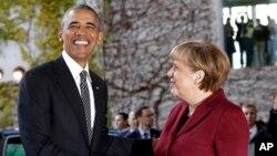 ປະທານາທິບໍດີ Barack Obama, ຊ້າຍ, ຖືກຕ້ອນຮັບໂດຍ ນາຍົກລັດຖະມົນຕີເຢຍຣະມັນ ທ່ານນາງ Angela Merkel ກ່ອນໜ້າກອງປະຊຸມຜູ້ນຳປະເທດ.