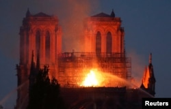 Fire fighters douse flames of the burning Notre Dame Cathedral in Paris, April 15, 2019.