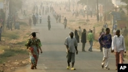 Quelques habitants de la ville marchent sur l'une des principales artères de Mbuji Mayi, chef-lieu de la province du Kasaï Oriental, 30 juillet 2006.