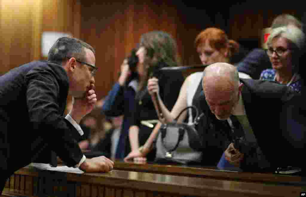 Oscar Pistorius talks with his uncle Arnold Pistorius during his murder trial in Pretoria, May 13, 2014.
