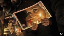 Supporters of Pakistan's slain leader Benazir Bhutto hold candles and her portraits at a ceremony to mark the third anniversary of her death in Islamabad, Pakistan, Dec. 27, 2010.