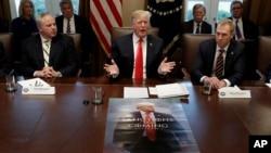 Predsednik Tramp na sastanku kabineta u Beloj kući, dok se na stolu ispred nalazi poster s njegovim likom (Foto: AP/Evan Vucci)