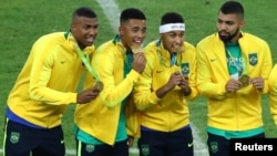 FILE - Neymar, second from right, and his Brazil teammates pose with their gold medals after defeating Germany to win the Olympics soccer final in Rio de Janeiro, Brazil, Aug. 20, 2016.