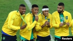 Neymar, second from right, and his Brazil teammates pose with their gold medals after defeating Germany to win the Olympic soccer final in Rio de Janeiro, Brazil, Aug. 20, 2016.