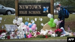 A student looks for a place to leave flowers at a makeshift memorial for the victims of the Sandy Hook Elementary School shooting at the entrance of Newtown High School December 18, 2012 in Newtown, Connecticut.