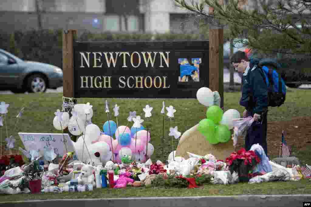 2012年12月18日,在紐敦高中入口為桑迪.胡克小學槍殺案死難者建立的臨時紀念地點﹐一名學生正在尋找安放鮮花的位置。