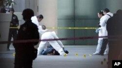 Nhân viên pháp y xem xét một thi thể sau vụ nổ súng chết người tại sân bay quốc tế Mexico City, ngày 25/6/2012