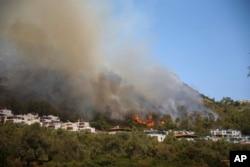 Wildfires rage Cokertme village, near Bodrum, Mugla, Turkey, Tuesday, Aug. 3, 2021. (AP Photo/Emre Tazegul)