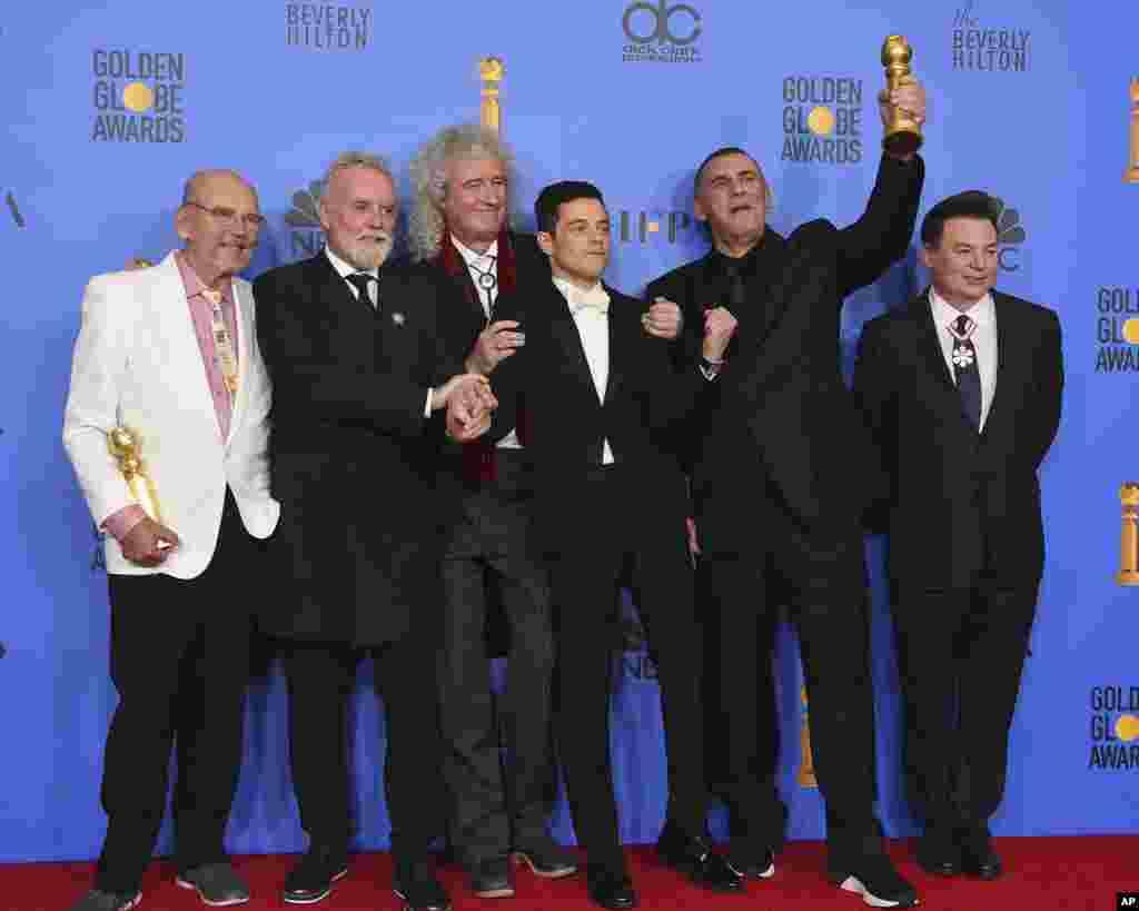 Джим Бич (слева направо), Роджер Тейлор, Брайан Мэй, Рами Малек, Грэм Кинг и Майк Майерс позируют в прессе с наградой за лучший фильм - драму «Богемская рапсодия рапсодия» (фото: Jordan Strauss/Invision/AP)