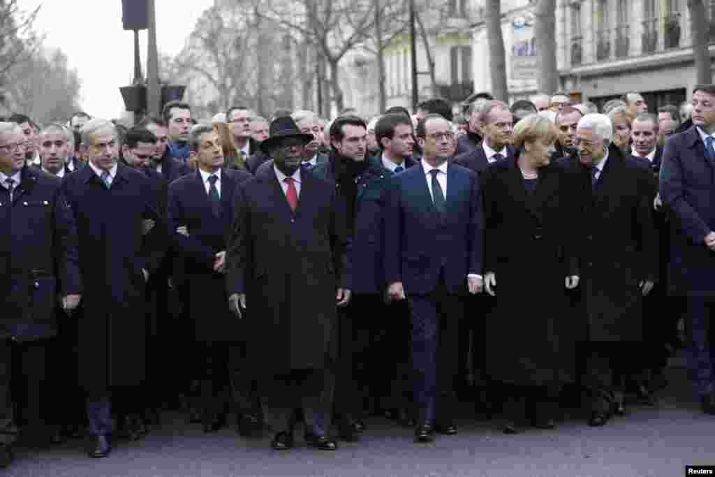 French President Francois Hollande is surrounded by head of states as they attend the solidarity march in the streets of Paris, Jan. 11, 2015.