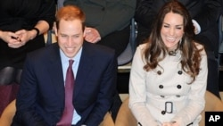 Britain's Prince William and his fiance Kate Middleton applaud as they watch a play at the Youth Action Centre in Belfast, Northern Ireland, Tuesday March 8, 2011.