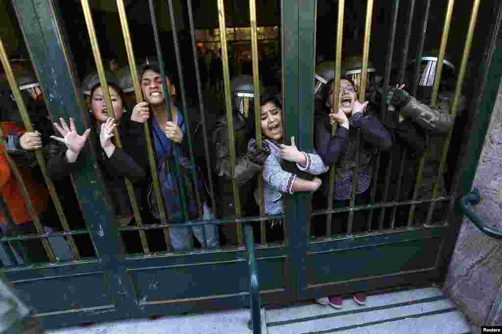Students cling at a fence while they are detained at the Education Ministry building during its occupation in downtown Santiago, Chile. Around 15 students occupied the building as part of a protest against a financial crisis at their university.