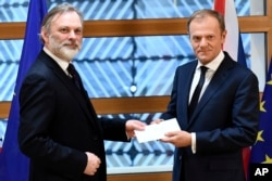 EU Council President Donald Tusk, right, gets British Prime Minister Theresa May's formal notice to leave the bloc under Article 50 of the EU's Lisbon Treaty from UK Permanent Representative to the EU Tim Barrow in Brussels, Wednesday, March 29, 2017.