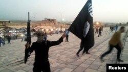 이라크 모술에서 ISIL 무장대원이 깃발을 휘날리고 있다. (자료사진)