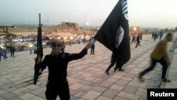 FILE - An Islamic State fighter holds up an IS flag and a weapon on a street in Mosul, Iraq, June 23, 2014.