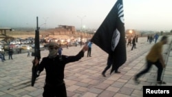 FILE - A fighter of the Islamic State group holds an IS flag and a weapon on a street in the city of Mosul, Iraq, June 23, 2014.