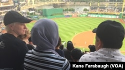 Michelle Boehm, a mentor and friend of Kazam Hashimi's family, attend Hello Neighbor's Refugee and Immigrant Night at PNC Park, a first for the Pittsburgh Pirates baseball organization, Aug. 1, 2017, in Pittsburgh.