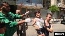 Bé trai Palestine bị thương trong vụ không kích của Israel được đưa vào bệnh viện.
