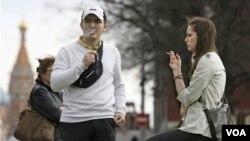 Dua anak muda sedang merokok di Kremlin, Moscow. Pemerintah Rusia berencana menaikkan pajak tembakau guna mengurangi jumlah perokok.