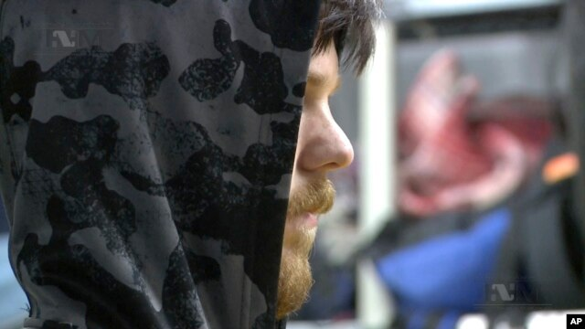 This frame grab from Jan. 28, 2016 taken from a video provided by Mexico's Instituto Nacional de Migracion, INM, shows a hooded Ethan Couch as he is processed by Mexican immigration agents, in Mexico City.