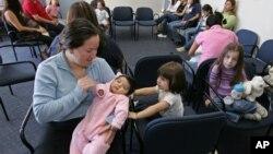 Imigran Meksiko Alejandro Ruiz of Michoacan menggendong bayinya yang berusia dua bulan, Antonia, di ruang tunggu rumah sakit di Salinas, California.
