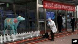 ایک غیر ملکی صحافی چین کے دارالحکومت بیجنگ میں ایک ڈیری فیکٹری میں داخل ہونے کے لیے ماسک پہن رہا ہے۔ 27 فروری 2020