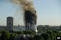 FILE - In this June 14, 2017 file photo, smoke rises from a 24-story high-rise apartment building on fire in London.