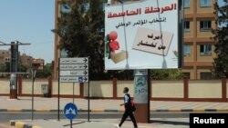 """Seorang warga melintasi papan pengumuman Pemilu Libya yang bertuliskan """"Tahapan Penting: Pemilu Parlemen Nasional - Anda Harus Tahu Siapa yang Anda Pilih"""" 19 Juni 2012. Komisi Pemilu Libya menunda Pemilu selama 18 hari dari tanggal ini."""