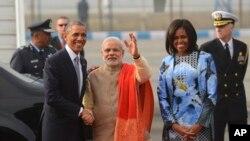 លោកប្រធានាធិបតីអាមេរិក បារ៉ាក់ អូបាម៉ា (ឆ្វេង)ចាប់រលាក់ដៃជាមួយលោកនាយករដ្ឋមន្រ្តីឥណ្ឌា Narendra Modi (កណ្តាល) គ្រាដែលលោកស្រី Michelle Obama ឈរ ក្បែរពួកអស់លោក នៅពេលដែលអស់លោកទៅដល់ស្ថានីយ៍កងទ័ពអាកាសPalam ក្នុងទីក្រុង New Delhi នៃប្រទេសឥណ្ឌា នៅថ្ងៃទី២៥ ខែមករា ឆ្នាំ២០១៥។