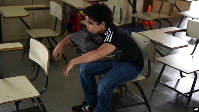 In this Friday, Oct. 13, 2017 photo, a student sits alone in a classroom at Ramon Marin Sola Elementary School, which opened its doors as a daytime community center after the passing of Hurricane Maria in Guaynabo, Puerto Rico. (AP Photo/Carlos Giusti)