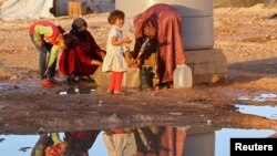 FILE - Syrian refugees collect water at Al Zaatri refugee camp near the border with Syria, in the Jordanian city of Mafraq.