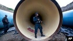 Un policía vigila una tubería de drenaje en las afueras de la prisión del Altiplano, en Almoloya, al oeste de la Ciudad de México.