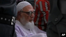 Bangladesh's Islamic party Jamaat-e-Islami former chief Ghulam Azam, on wheelchair, is escorted by security people to a court in Dhaka, July 15, 2013.