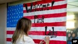 Premyè Dam Melania Trump ap Siyen yon Drapo Ameriken nan Sant UPBRING NEW HOPE la, nan Tegzas.AP/Andrew Harnik, 21 Jen, 2018.