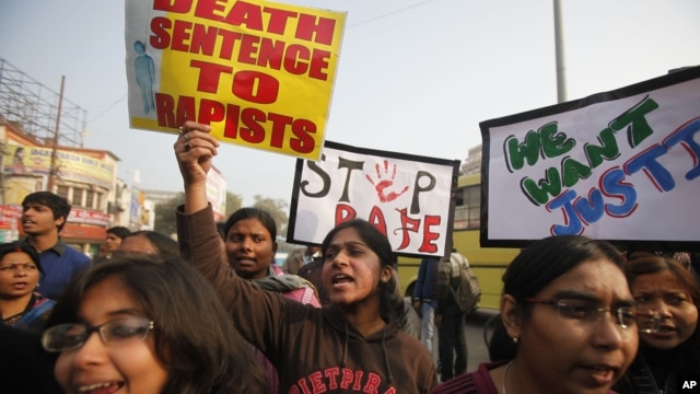 ndian students protesting against the brutal gang-rape of a woman on a  bus last week in New Delhi, hold placards during a protest in Allahabad, India, Dec. 26, 2012