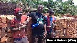 Benjamin Kamulete, l'initiateur de la fabrication des briques écologiques, poste avec quelques jeunes qu'il a initiés dans la production des briques écologiques, à Bukavu, Sud-Kivu, 2 janvier 2017. (VOA/ Ernest Muhero)