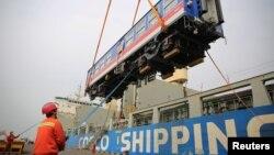 中國山東省青島港的工人將一輛出口斯里蘭卡的高鐵車廂裝入集裝箱裡。(2020年3月3日)