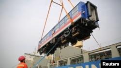 中國山東省青島港的工人將一輛出口斯里蘭卡的高鐵車廂裝入集裝箱里。 (2020年3月3日)
